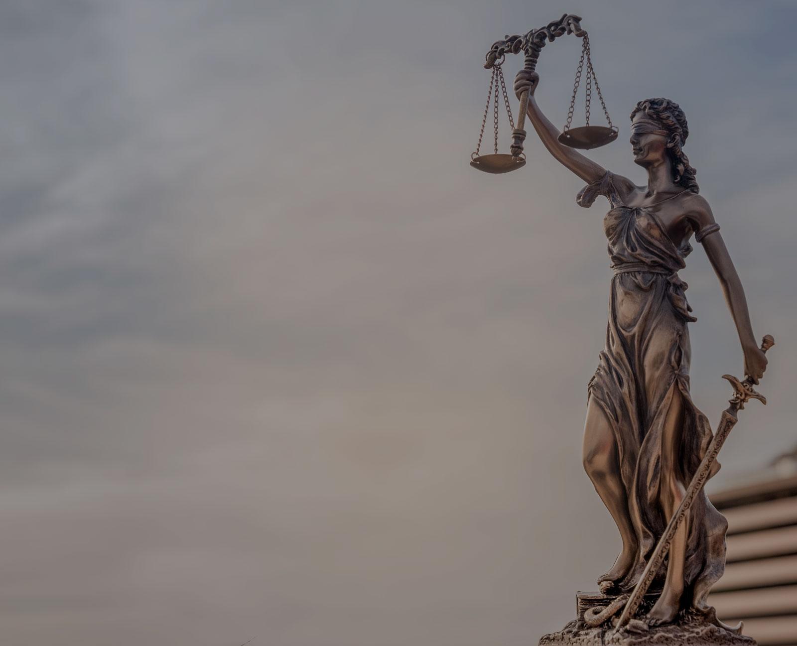 Estátua da justiça com venda nos olhos, balança na mão direita levantada e espada na mão esquerda em posição de descanso.